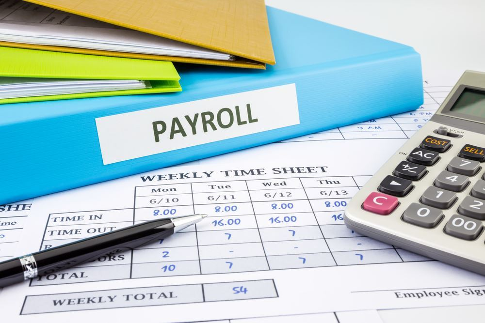 Payroll book, calculator and weekly time sheet laid out