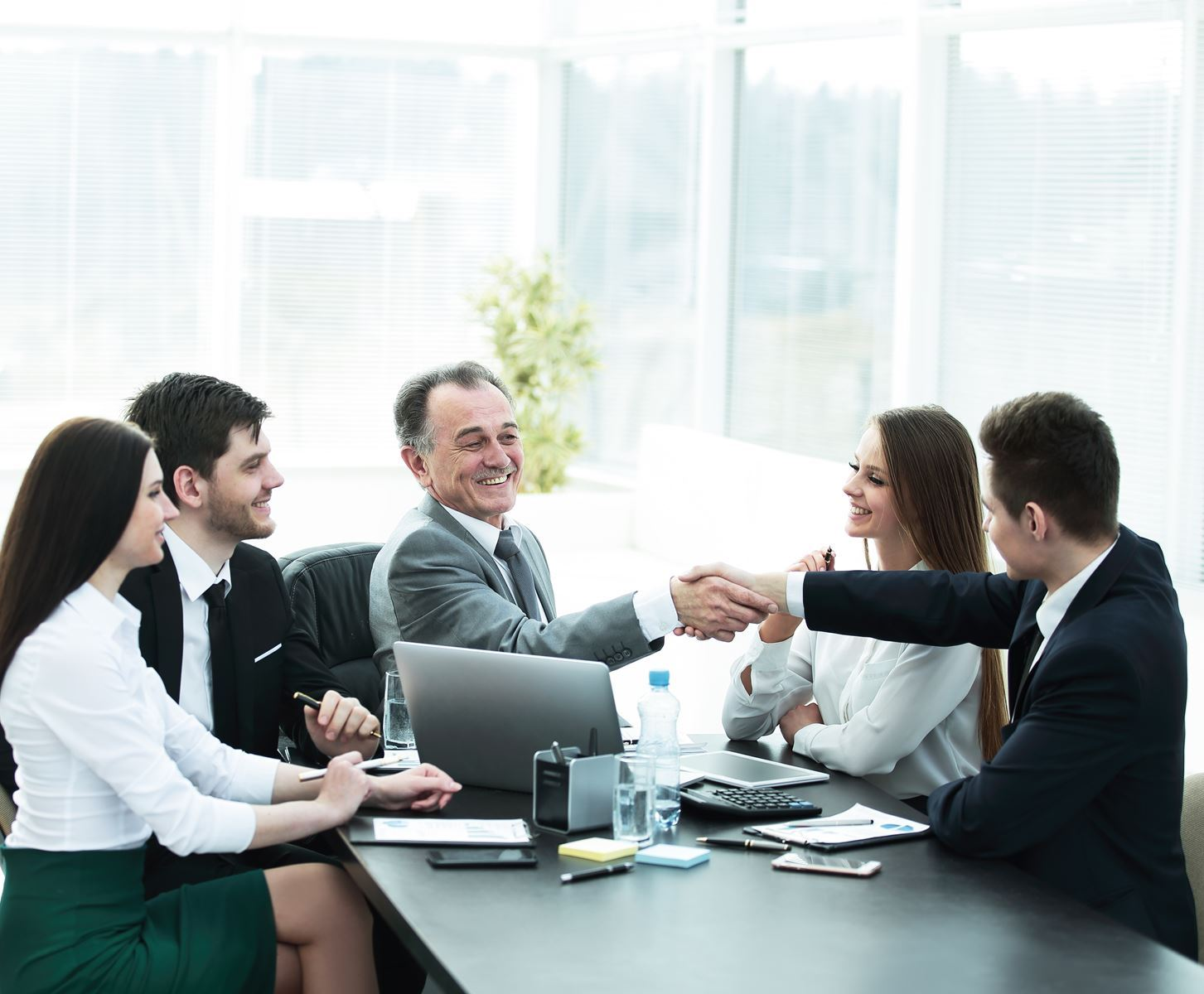 Group of people in a meeting sitting at a table. 2 men are shaking hands